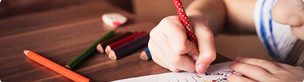 Fotografía de una niña haciendo un dibujo con lápices de colores