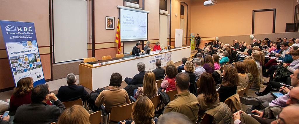 Foto panoramica que muestra al público y tres de los ponentes