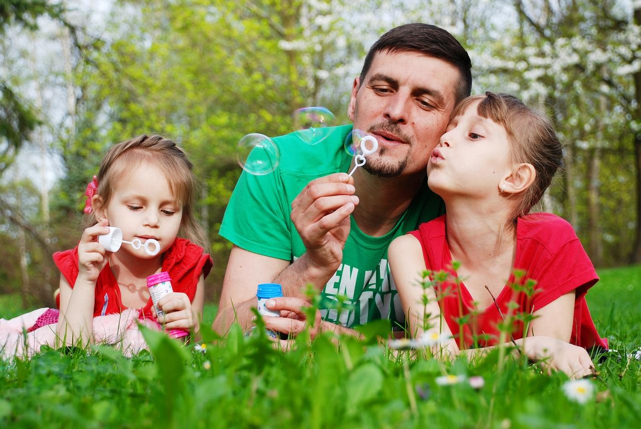 Foto de un padre jugando con sus hijas