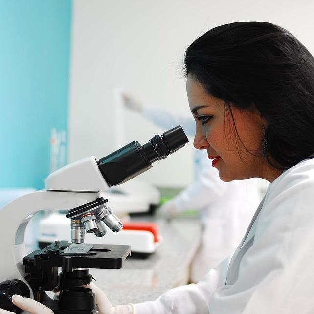 Foto de una investigadora mirando por un microscopio
